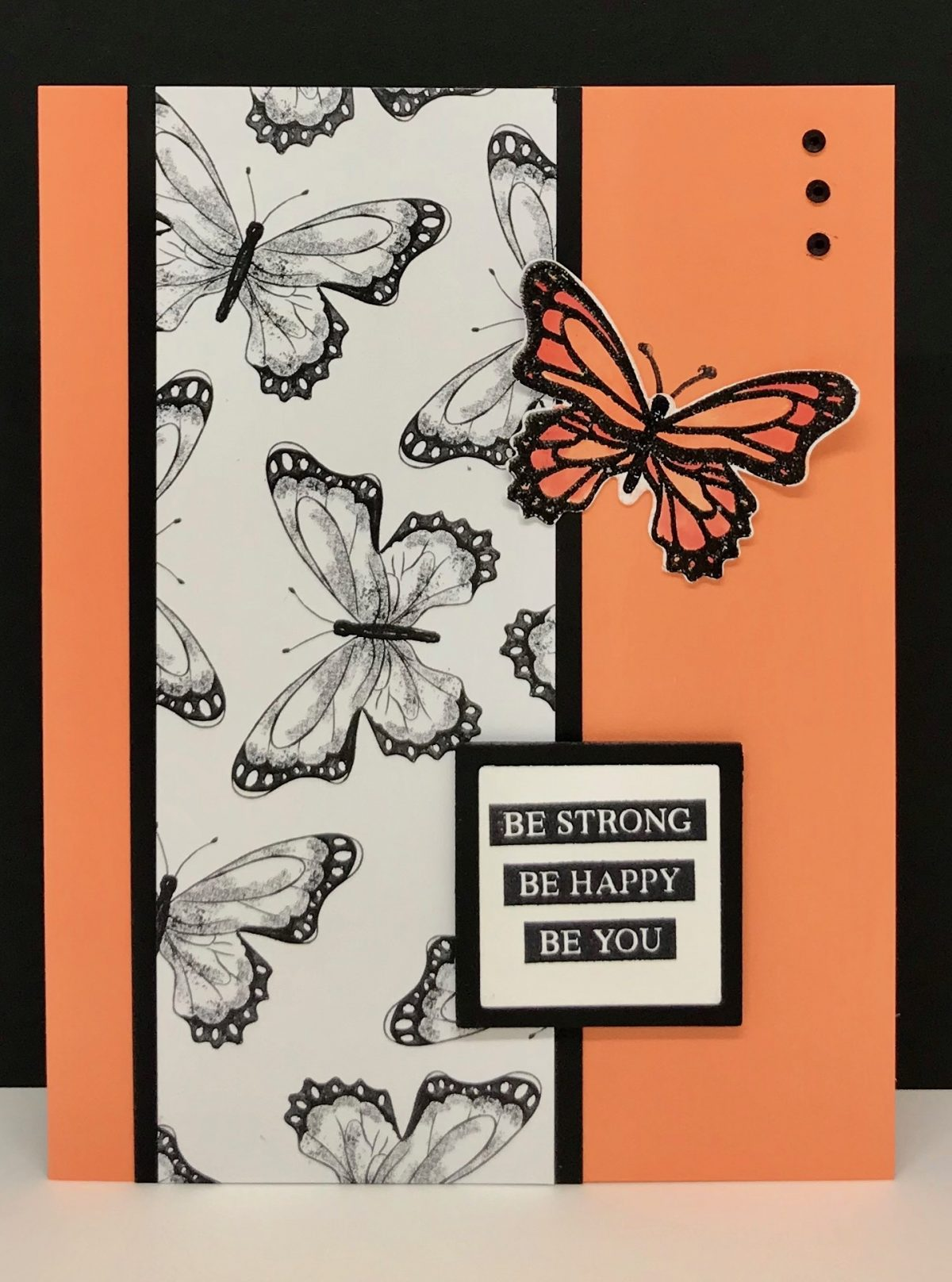 Black and White strip of butterfly designer paper with offset orange colored butterfly. Sentiment Be Strong, Be Happy, Be You