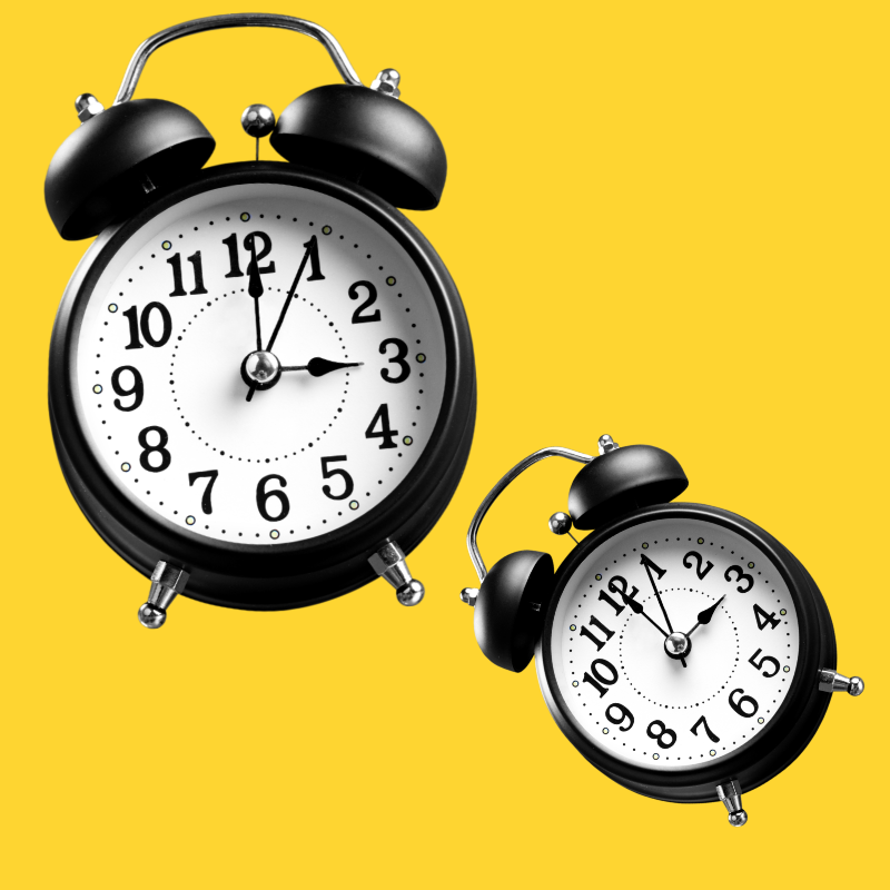 Two black alarm clocks on a yellow background