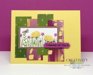 A cheerful Daffodil Delight greeting card base with bright green, magenta and yellow designer paper in the background of the Field of Flowers focal point. Sentiment reads 'Thinking of You.'