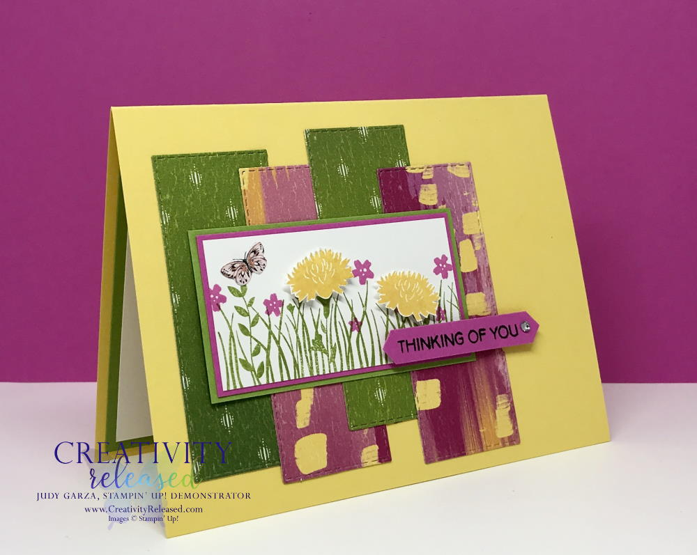 A Daffodil Delight greeting card base with bright green, magenta and yellow designer paper in the background of the Field of Flowers focal point. Sentiment reads 'Thinking of You.'
