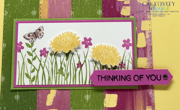 An up-close look at the focal point of A Daffodil Delight greeting card base with bright green, magenta and yellow designer paper in the background of the Field of Flowers focal point. Sentiment reads 'Thinking of You.'