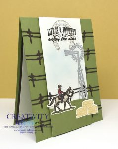 "A side view of a Texas-style card with fencing across an Old Olive card base. The white center panel displays a cowboy on a horse, bales of hay and a windmill, all from the Stampin' Up! stamp set ""Ride The Range"""