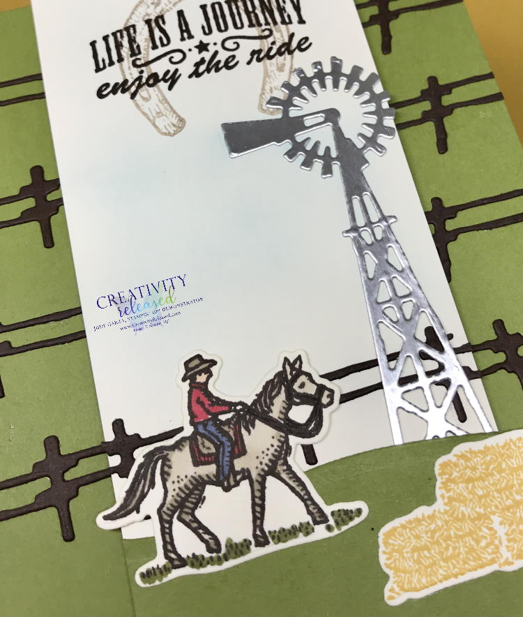 "An up-close view of a Texas-style card with fencing across an Old Olive card base. The white center panel displays a cowboy on a horse, bales of hay and a windmill, all from the Stampin' Up! stamp set ""Ride The Range"""