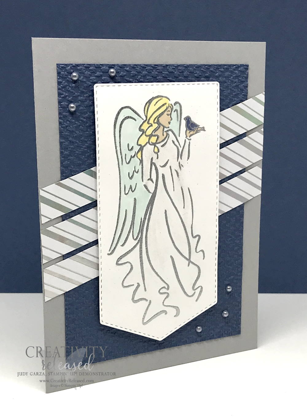 Side view of a Christmas card with an angel in a flowing robe stamped on a banner and , accented by strips of shiny, silver-striped DSP. All images are from Stampin' Up!