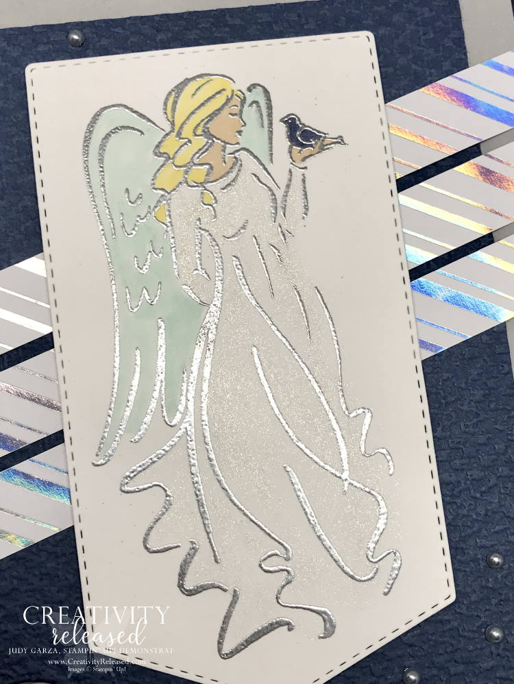 An up-close look at a Christmas card with an angel in a flowing robe stamped on a banner and , accented by strips of shiny, silver-striped DSP. All images are from Stampin' Up!