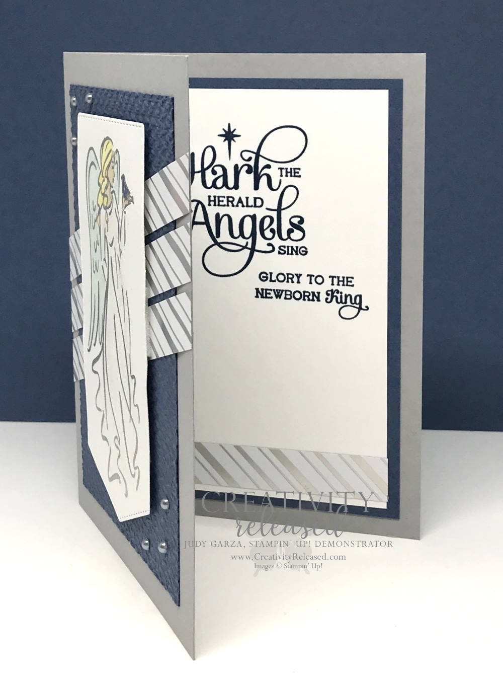 A partially open view of a Christmas card with an angel in a flowing robe stamped on a banner and , accented by strips of shiny, silver-striped DSP. All images are from Stampin' Up!